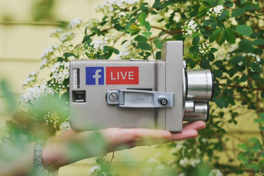 """altere Kamera mit Aufklebers des Facebook Symbols und den Schriftzug """"Live"""""""