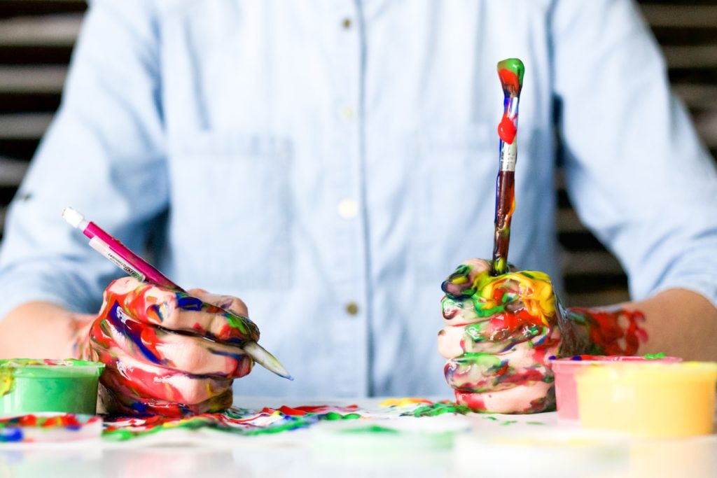 Mensch mit farbverschnierten Händen hält Pinsel und Stift