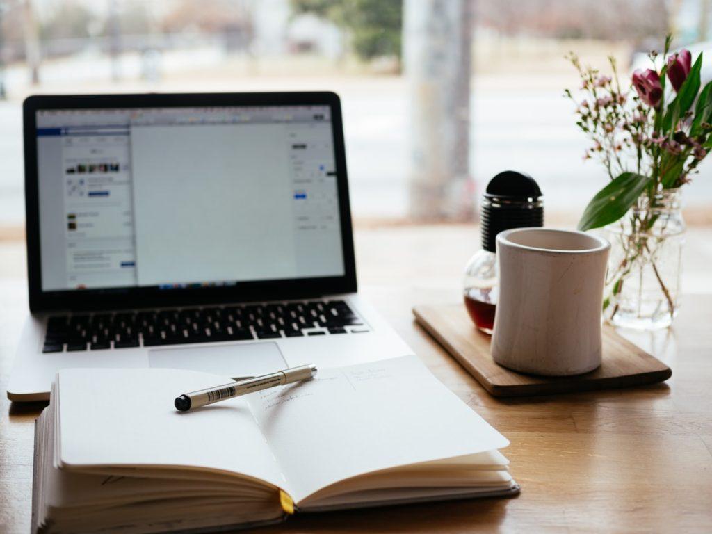 Laptop und aufgeschlagenes Notizbuch