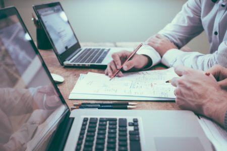 Zwei Personen arbeiten am Laptop und auf Papier