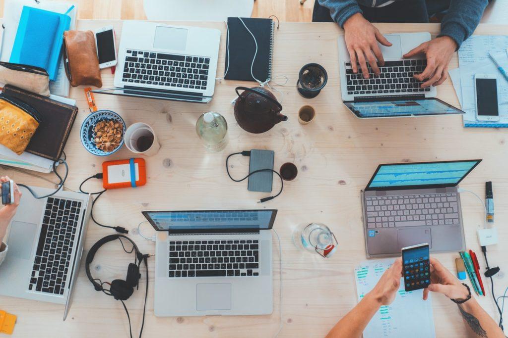 mehrer Personen arbeiten gemeinsam an einem großen Tisch