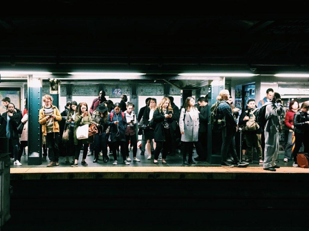 Menschen warten auf die Bahn am Bahnsteig