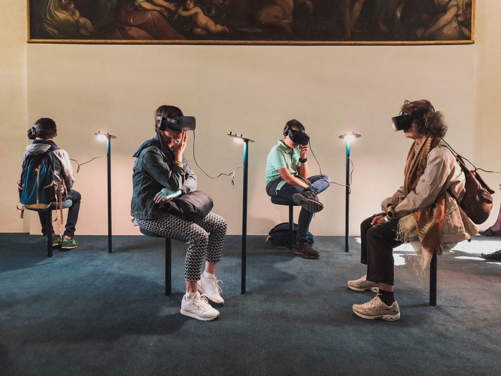 4 Personen sitzen in einem Raum mit Augmented Reality Brillen